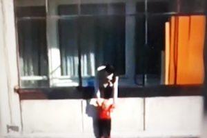 Младото момиче държи детето за ръцете и го провесва от балкона