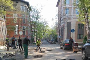 Работници със сигнални жилетки хвърлят с лопати нещо в дупките