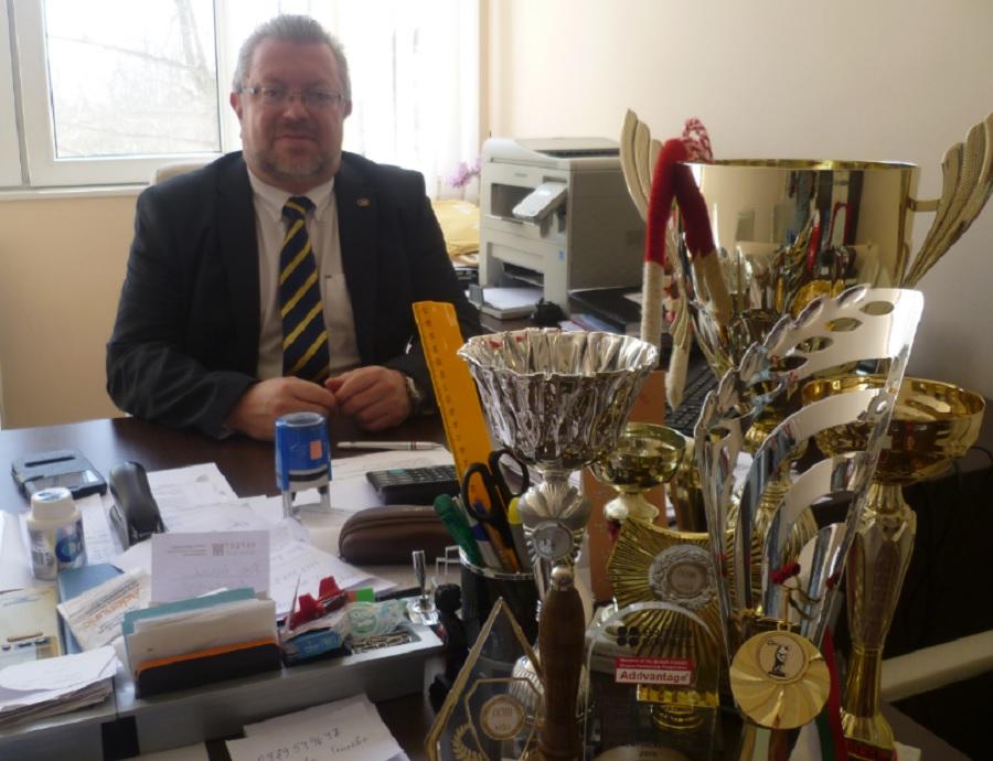 Николай Радев е наредил на бюрото си купите, спечелени от негови ученици