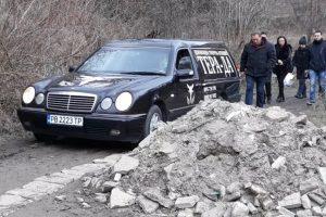 Катафалката заобикаля купчините със строителни отпадъци по пътя към гробището в Руен.