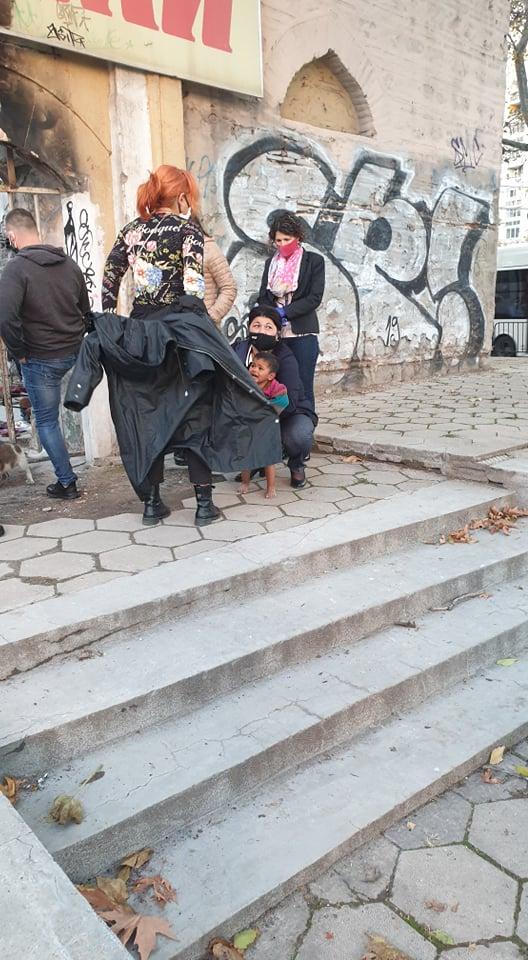 Социална работничка зави детето с якето си.