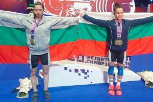 Шампионката Надежда-Мей Нгуен (вдясно) и вицешампионката Ивана Петрова позират с българския трибагреник след двойния триумф на тима ни в откриващата категория от Евро `21 по вдигане на тежести.